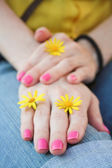 Women's hands with pink manicure and yellow flowers — Stock Photo