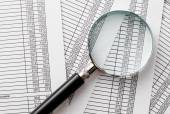 Single Magnifying Glass on Top of Business Reports — Stock Photo