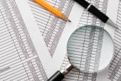 Magnifying Glass, Pen and Pencil on Top of Reports — Stock Photo