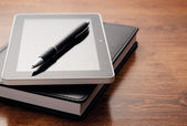 Tablet Device on Notebook at Wooden Table — Stock Photo