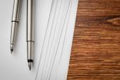 Pens and Sheets on Wooden Table with Copy Space — Stok fotoğraf