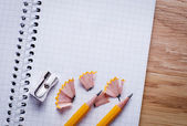 Pencils, pencil sharpener and unfolded notebook on office desk — Stock Photo