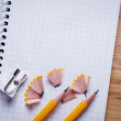 Pencils, pencil sharpener and unfolded notebook on office desk — Stock Photo #60850467
