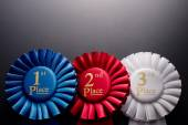 Three places pleated ribbon rosettes — Stock Photo