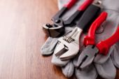 Adjustable wrench, pliers and nail puller on top of the protective gloves — Stock Photo