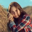 Girl rests against haystack — Stock Photo #57676683