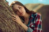 Girl rests against haystack — Stock Photo