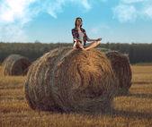 Young woman meditating on haystack — Stock Photo