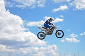 X games driver standing on the MX motorcycle is flying over the  — Stock fotografie