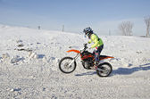 Winter Motocross racer rides standing up on the rear wheel — Zdjęcie stockowe