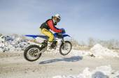 MX winter rider soars from a hill looking back — Foto Stock