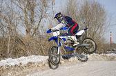 Motocross, pilota motociclistico vola sopra la collina fuori dalla neve — Foto Stock
