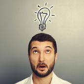 Man looking up at drawing light bulb — Stock Photo
