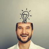 Man looking up at light bulb — Stock Photo