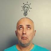Senior man looking at light bulb — Stock Photo