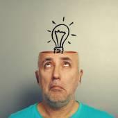 Senior man looking up at light bulb — Stock Photo