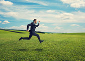 Smiley businessman in suit running fast — Stock Photo