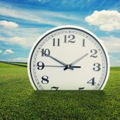 Clock in the green grass over blue sky — 图库照片