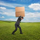 Man carrying two heavy boxes at outdoor — Stock Photo