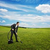 Smiley businessman vacuuming green grass — Foto Stock