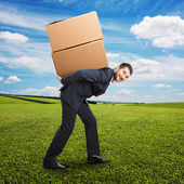 Businessman holding packages on the back — Stock Photo