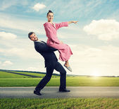 Woman sitting on man and pointing at the way — Stock Photo