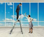 Woman and businessman on stepladder — Stock Photo