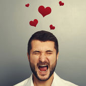 Screaming man with red hearts — Stock Photo