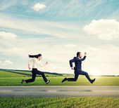 Man and woman in formal wear running — Stock Photo