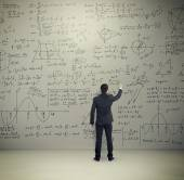 Man in formal wear writing formulas — Stock Photo