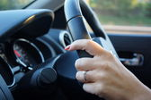 Female hands controlling steering wheel — Stockfoto