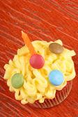 Fancy birthday cupcake with orange candle — Stock Photo