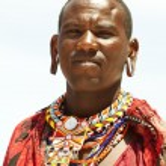 Young massai warrior man posing on bright sunny beach in Kenya — Stock Photo #56054487
