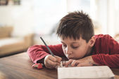 Boy doing homework reluctantly — Stock Photo