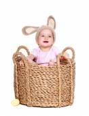 Baby girl easter rabbit sitting in a basket — Stock Photo