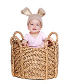 Baby girl easter rabbit sitting in a big basket — Stock Photo