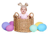 Baby wearing  rabbit hat sitting in a basket with giant easter eggs — Stock Photo