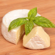 Brie cheese with a basil — Stock Photo #58975993