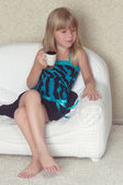 Girl 5 years old sitting on a sofa with cup — Stock Photo