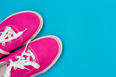 Part of the Pink sneakers with white laces on a blue — Stock Photo