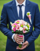 Groom holding wedding flowers — Stock Photo