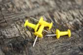 Yellow push pins on old wooden background — Stock Photo