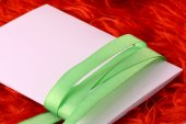 Greeting card with white paper and green bow — Stock Photo