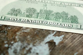 Close-up of a 100 dollars banknotes on wooden background — Stock Photo