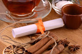 Tea cup with white paper and cinnamon — Stock Photo
