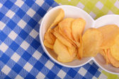 Close-up of fresh, crispy potato chips in a wooden bowl on a white background. — Stock Photo