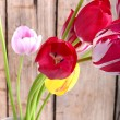 Bouquet of red tulips against a wooden background, close up flowers — Stock Photo #76714143