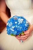 The bride holding a bouquet which lie wedding rings — Stock Photo