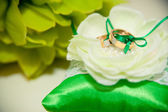 Wedding rings lie on a green cushion for rings — Stock Photo