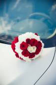 Bridal bouquet  lying on the hood of a car — Stock Photo